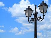 Viejo farol calle decorada contra nublado cielo azul — Foto de Stock