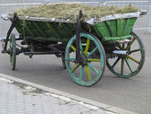 Old vintage green wooden wagon with hay — 图库照片