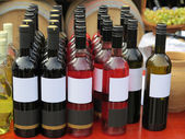 Red empty label wine bottles in rows — Stock Photo