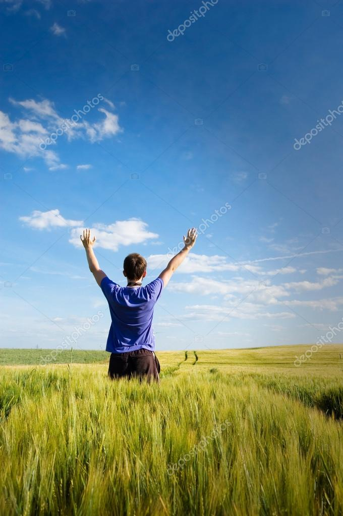 Man standing on the green field at summer and feel the freedom. — Stock Photo #14612569