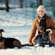Happy smilling girl with dog sitting on the snow — Stock Photo