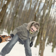 Girl playing with dog on the snow - Foto de Stock