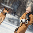 Girl playing with dog on the snow — Stock Photo