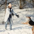 Girl playing with dog on the snow — Stock Photo #14868983