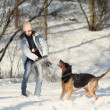 Stock Photo: Girl playing with dog on snow