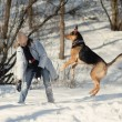 Girl playing with dog on the snow — Stock Photo #14868995