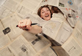 Girl engulfed with newspapers and holding pen in the hand — Stock Photo