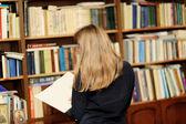 Una giovane donna nella libreria leggendo un libro — Foto Stock