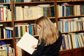 A young woman in the library reading a book — Stock Photo
