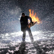 Man with chainsaw in the hands on the night snow background — Stock Photo