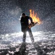 Man with chainsaw in the hands on the night snow background - Stock Photo