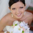 Happy smiling bride with bouquet of flowers — Stock Photo #20006827