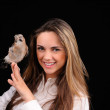 Portrait of smiling girl with bird on the hand — Stock Photo