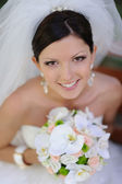 Happy smiling bride with bouquet of flowers — Stock Photo