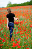 Girl with basket on poppy field — Stock Photo