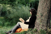 Happy young pregnant woman reading a book — Photo