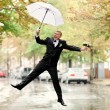 Bridegroom jumping with white umbrella — Stock Photo
