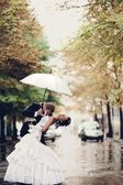 Bride and groom kissing under white umbrella — Stock Photo
