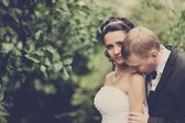 Bride and groom kissing outdoor — Stock Photo