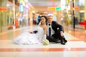 Bride and groom sitting on the floor — Stock Photo