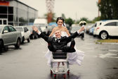 Happy bride pulling a fiance in the pushcart — Stock Photo