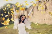 Young attractive bride throws yellow leaves — Stock Photo