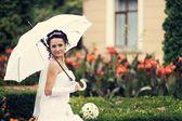 Young attractive bride with white umbrella — Stock Photo