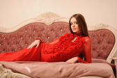 Alluring woman relaxing on a sofa in luxury interior — Stock Photo