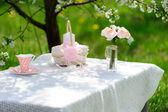 Blumenstrauß aus Rosen und Tasse auf dem Tisch im Garten — Stockfoto