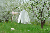 White coat, basket and bouquet in garden  — Stockfoto