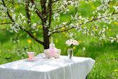 Bukiet róż i kubek na stole w ogrodzie — Zdjęcie stockowe