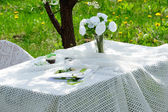 Bouquet of roses and  cake on plate on the table in the garden — Zdjęcie stockowe
