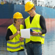 Stock Photo: Dockers checking freight papers