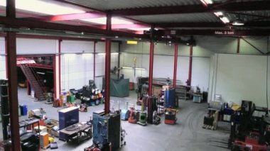 Pan through a large mechanics workshop, seen from a high point of view