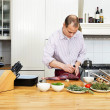 Stock Photo: Man Cutting Meat On Chopping Board