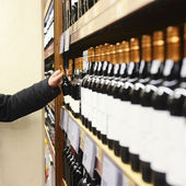 Man Choosing Wine Bottle From Shelves In Store — Foto Stock