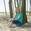 Woman sitting on beach — Stockfoto