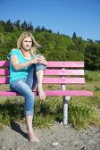 Plajda bankta oturan genç kadın — Stok fotoğraf
