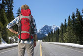 Backpacker on mountain road — Stock Photo