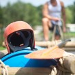 Stock Photo: Helmet and oar on inflatable raft