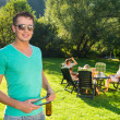 Man Holding Tongs And Wine Bottle At Garden Party — Stock Photo