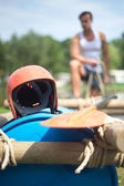 Helmet and oar on inflatable raft — Stock Photo