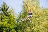 Happy Woman Hanging On Zip Line In Forest — Stock Photo