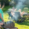 Friends enjoying barbecue in garden — Stok fotoğraf