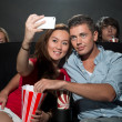 Couple watching movie at cinema and photographing themselves — Stock Photo