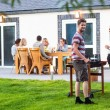 Friends preparing barbecue in back yard — Stock Photo