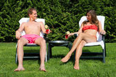 Couple sunbathing in back yard and drinking cocktails — Stock Photo