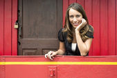 Woman Leaning On Railing In Red Caboose Car — Stock Photo