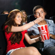 Woman Feeding Popcorn To Boyfriend In Theatre — Stock Photo