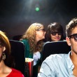 Woman Whispering In Boyfriend's Ear In Cinema Theatre — Stockfoto